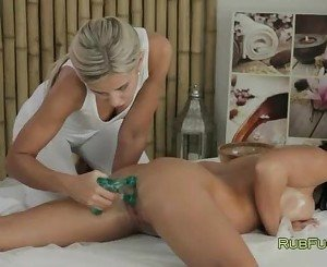 Lesbians fucking with massage tool on a table