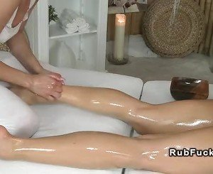 Masseuse rubs and oils sexy brunette on a massage table